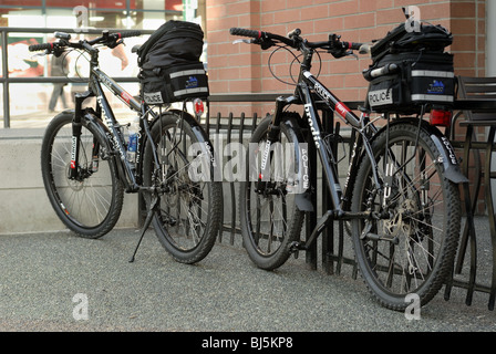Two Vancouver Police bicycles on its bike stand, up against a railing. - Stock Photo