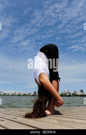 flexible woman stretching bending over outdoors stock