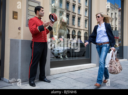 A Turkish bellboy salutes a shopping beautiful young woman in Maximiliastrasse Munich, Germany - Stock Photo