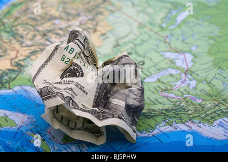 Throwing money away. A hundred dollar bill on a world map - Stock Photo