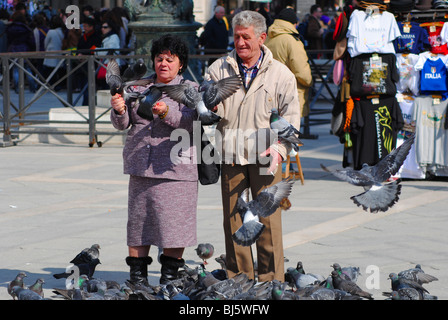 Tourists feed pigeons in St Mark's Square, Venice, Italy - Stock Photo