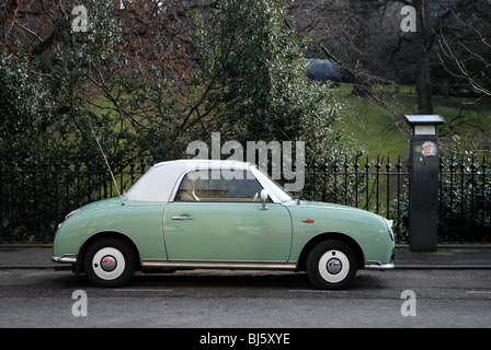 Green and white Nissan Figaro car parked in Edinburgh's New Town. - Stock Photo