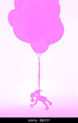 Rag doll holding onto helium balloons floating away. Pink Silhouette concept - Stock Photo