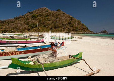Indonesia; Lombok; South Coast; Seong Blanak; fisherman mending nets on the beach - Stock Photo