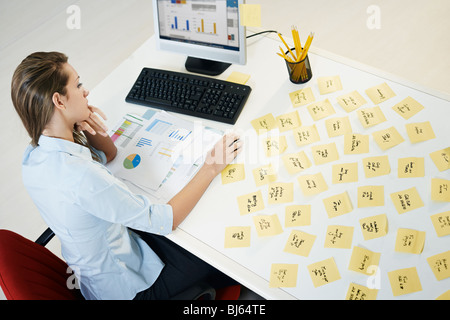 tired business woman with adhesive notes on table. High angle view - Stock Photo