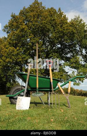 Wheelbarrow and garden tools in the garden - Stock Photo