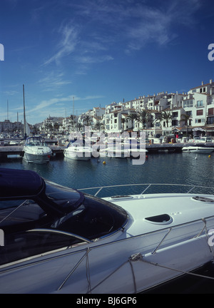 Luxury cabin cruisers in Puerto Banus marina with apartments and quayside shops beyond - Marbella, Spain - Stock Photo