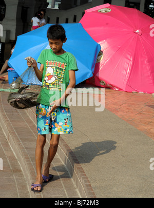 young boy selling cat fish for people to release in chao praya river (making merit)nonthaburi ,thailand - Stock Photo