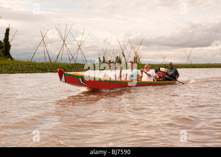 Indonesia, Sulawesi, Sengkang, Danaue Tempe Lake, three middle aged tourists in local dugout boat on sunset tour - Stock Photo