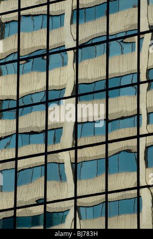 A concrete building reflected in the panes of glass on another office building. - Stock Photo