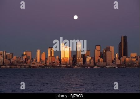 Seattle Skyline from West Seattle with Moonrise over city and Elliott Bay with city lights Seattle Washington State - Stock Photo