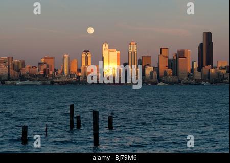 Seattle skyline from West Seattle with moonrise over Elliott Bay Washington State USA - Stock Photo