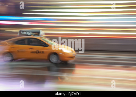 A yellow taxi cab is a blur as it rushes through the lights of Times Square at night in New York City. - Stock Photo