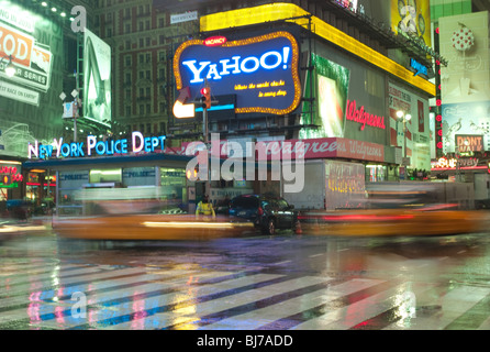 Taxis in motion rushing past the NYPD station in Times Square on a rainy evening in New York City. - Stock Photo