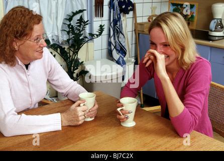 Women gossiping - friends women laughing kitchen - SerieCVS500202167 - Stock Photo