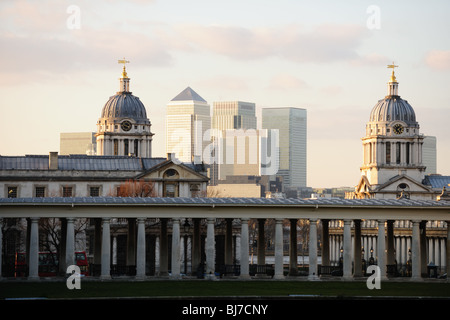 Towers of the Old Royal Naval College, Greenwich, London, UK, a world heritage site, with Canary Wharf in the background - Stock Photo