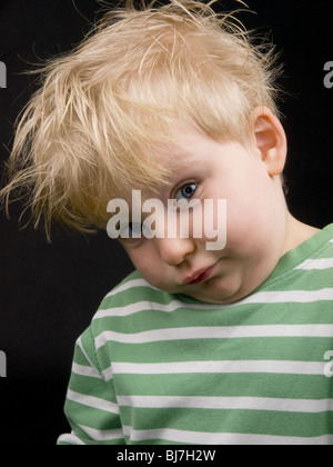 Little boy making funny face on black background. Boy have blue eyes and blond hair and have a bit of dirt on his - Stock Photo