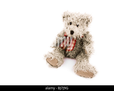 Teddy-bear with red bow on white background. On left side of picture it's empty space. - Stock Photo