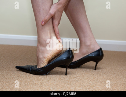 woman has pain in her feet and ankles - Stock Photo