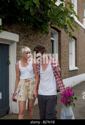 Couple walking home from flower market on a sunday afternoon in summer, london, uk, england, europe - Stock Photo