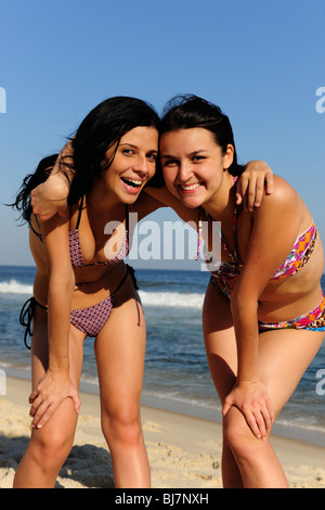 two happy girl friends laughing on the beach - Stock Photo
