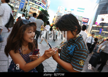 Japanese mother and son with their mobile telephones, Tokyo, Japan. - Stock Photo