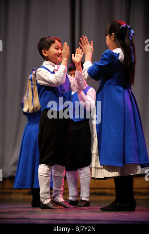 Primary school children competing in a welsh folk dancing competition in Eisteddfod, Wales UK - Stock Photo