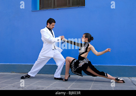 Two Professional Tango Dancers dressed in black and white against a plain blue wall  in La Boca Buenos Aires, Spain - Stock Photo