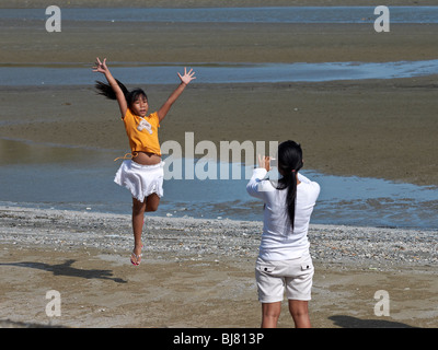 Mother photographing carefree jumping daughter at the beach. Thailand S. E. Asia. mother taking photograph child - Stock Photo