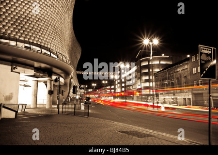 Traffic leaves light trails past selfridges in Birmingham city center at night. - Stock Photo