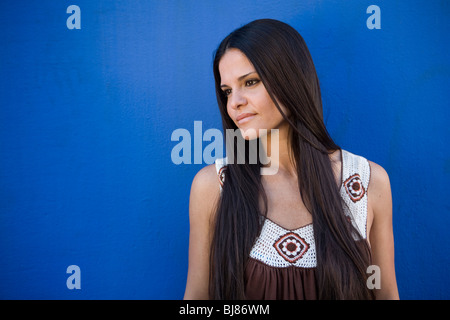 woman with long, dark, loose, straight hair posing against blue wall - Stock Photo