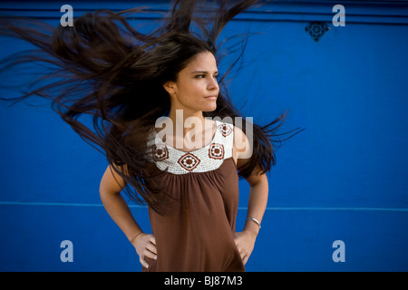 woman with wild, long, dark, straight, loose hair blowing in the wind - Stock Photo