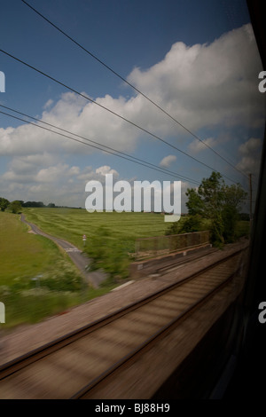 View of countryside from train, country road, green fields, blue sky, rail road - Stock Photo