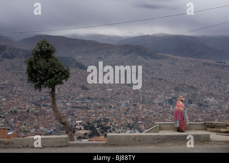 Indigenous woman looking out across la paz as seen from el alto, bolivia - Stock Photo