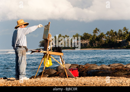 'Plein Air' artist painting at Lahaina Harbor Maui Hawaii.  Molokai in the background - Stock Photo