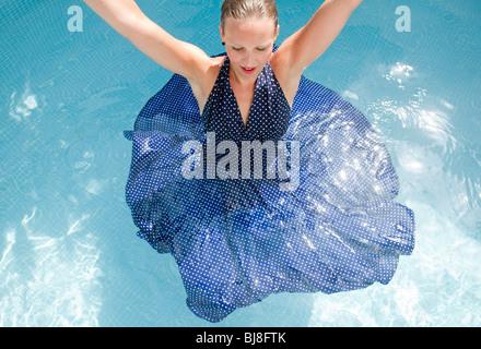 woman in blue polka dot dress dancing in swimming pool - Stock Photo