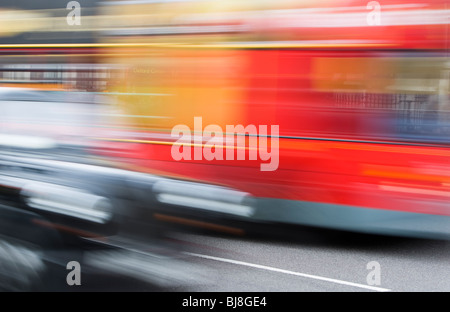 Taxi and Red Double Decker Bus Driving Down Street in London, Blurred Motion, transportation transport black red - Stock Photo