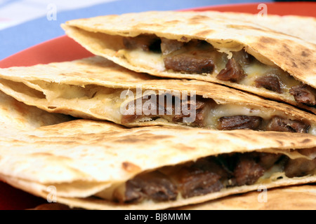 mexican quesadillas dinner or delicious snack,made with beef,corn tortilla,cilantro and onions on  fancy red mexican - Stock Photo