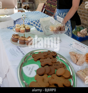 woman selling cakes, muffins, cupcakes and gingerbread men at a cake stand at a market - Stock Photo