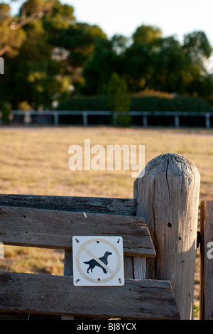No dogs allowed sign on a farm gate. - Stock Photo