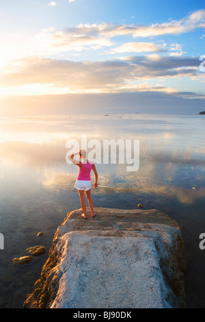 Girl standing at end of pier looking into sunset Matabungkay; Batangas; Southern Luzon; Philippines - Stock Photo