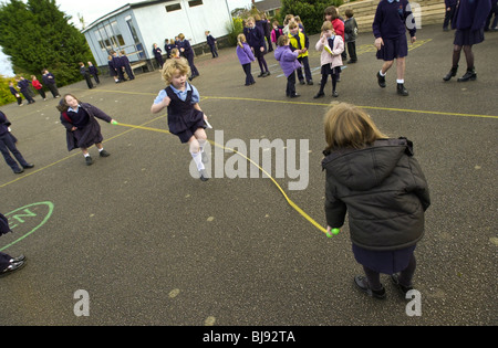 Skipping, traditional school playground game being played on the schoolyard of a primary school in Wales UK - Stock Photo