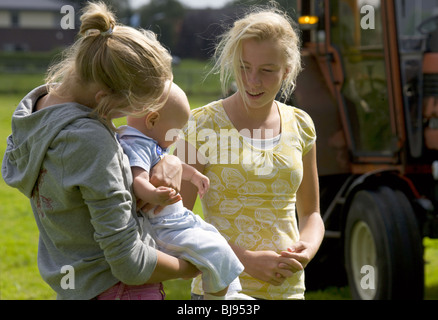 Underage teenage mum , the girl showing her baby to 12 years girl friend outside - Stock Photo