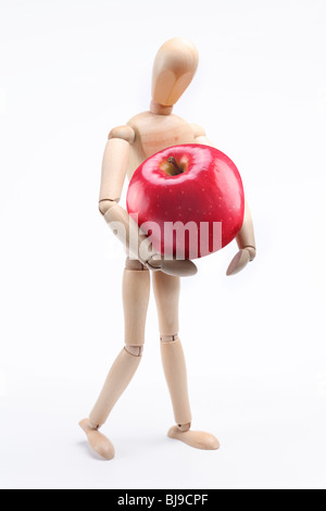 Wooden man holding a large red apple. Isolated over white - Stock Photo