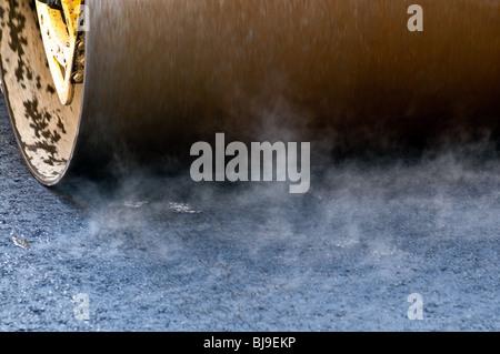 Making new road. Roller press fresh tar. Motion blur. - Stock Photo