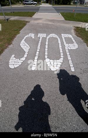 painted roadway stop sign Branford Florida along walking path - Stock Photo