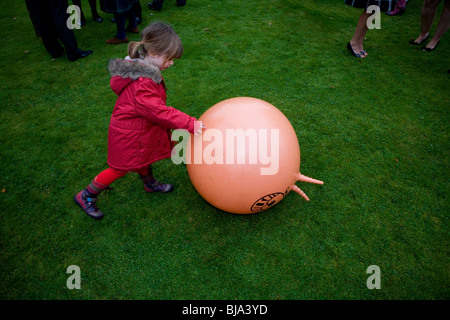 young girl in red coat playing on lawn with bouncing ball at adult's party - Stock Photo