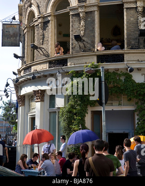 people gathered outside a public house and woman leaning out of a window - Stock Photo