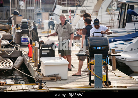 Men of mixed ages and races barbecuing at the Toronto waterfront - Stock Photo