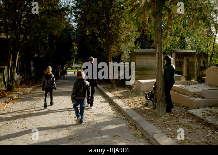 Paris, France - Young Family Walking in Urban Park, Pere Lachaise Cemetery, Monument - Stock Photo